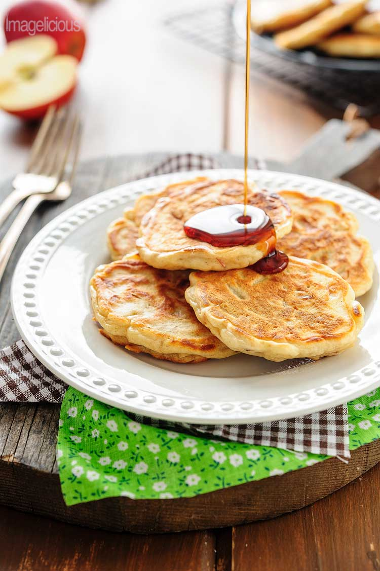 Plate with a few apple pancakes and maple syrup drizzle over them.