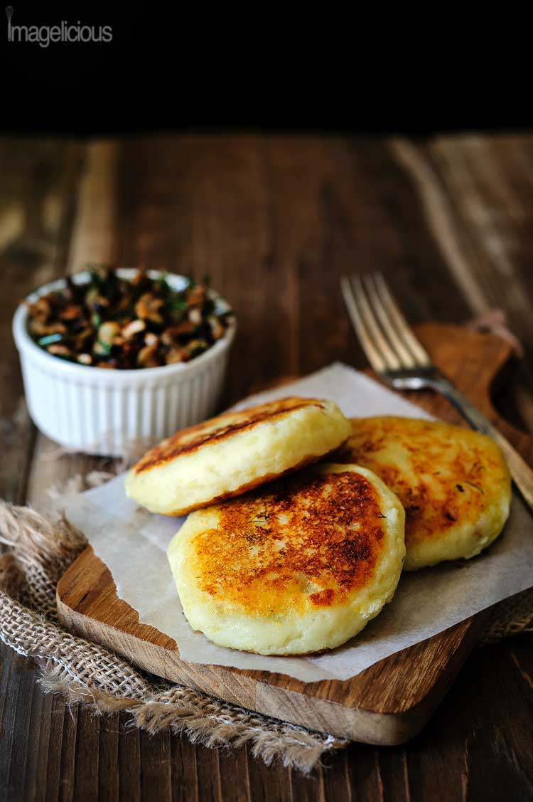 Three golden Vegan Potato Cakes stuffed with Mushrooms are on a cutting board. A bowl with mushroom stuffing is visible in the background
