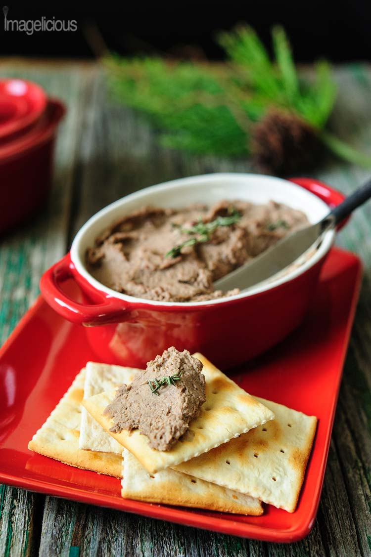 Chicken Liver Pâté with Apple and Thyme in a red little pot on a red plate with a few crackers in the front