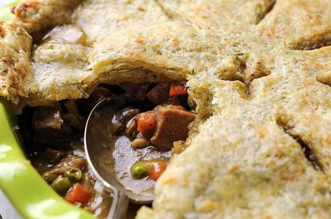 Beef Pot Pie with Cheddar Crust - Soft cubes of meat, melting into silky smooth gravy, studded with bright carrots and peas, mixed with earthy mushrooms, and occasional clove of sweet soft garlic, covered in flakey cheddar pastry with a hint of fresh dill. Perfect to use left over roast. Great way to celebrate St. Patrick's Day | Imagelicious