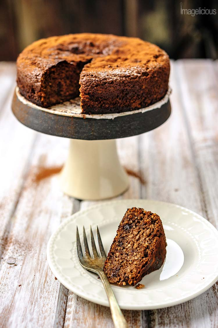 Small cake stand with a Gluten-Free Almond Ricotta Cake on it with a slice cut out. A slice is on the small plate in front of the cake stand