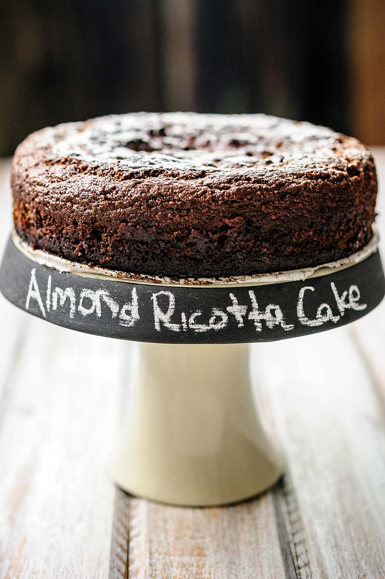 Close up of a small cake stand with a Gluten-Free Almond Ricotta Chocolate Cake. The Cake Stand has Almond Ricotta Cake written on the edge in chalk.