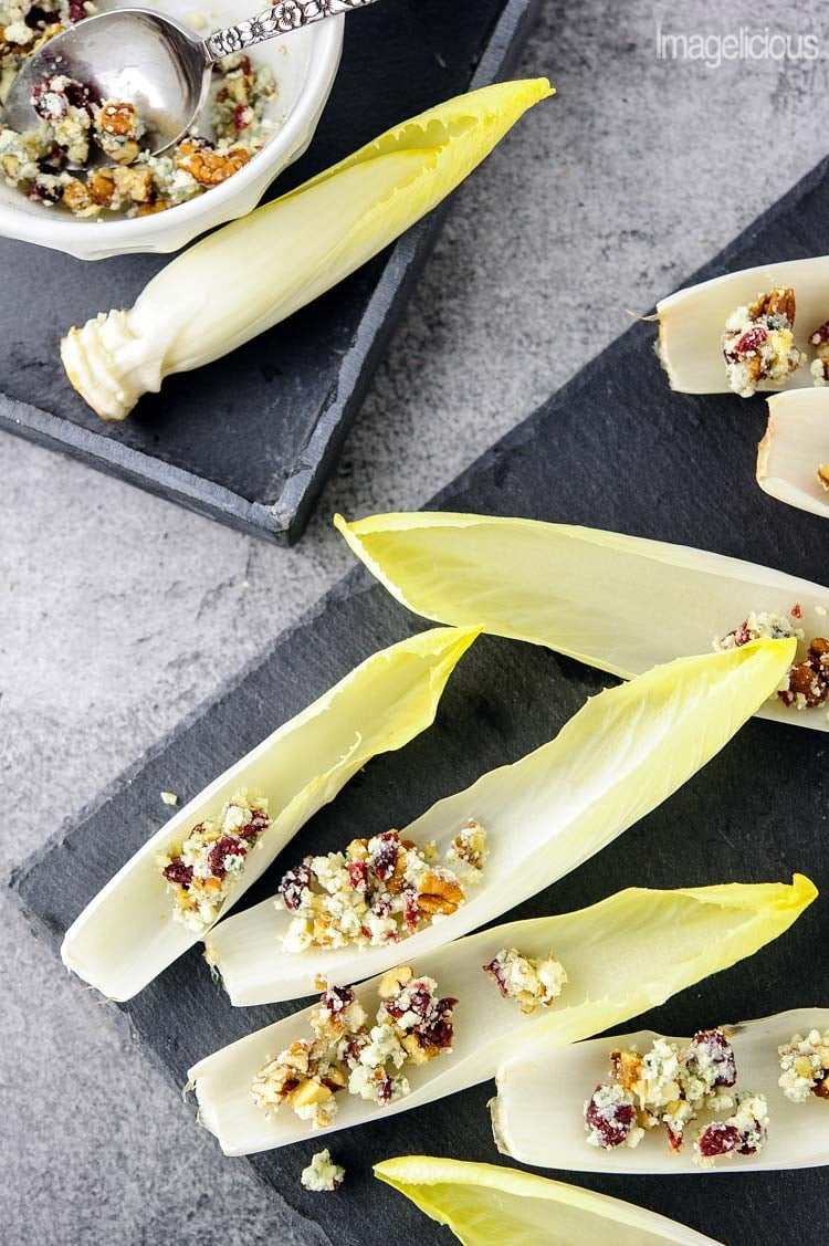 Top down view of endive appetizer boats with blue cheese, cranberries, and pecans. The rest of the blue cheese mixture is in a bowl to the side