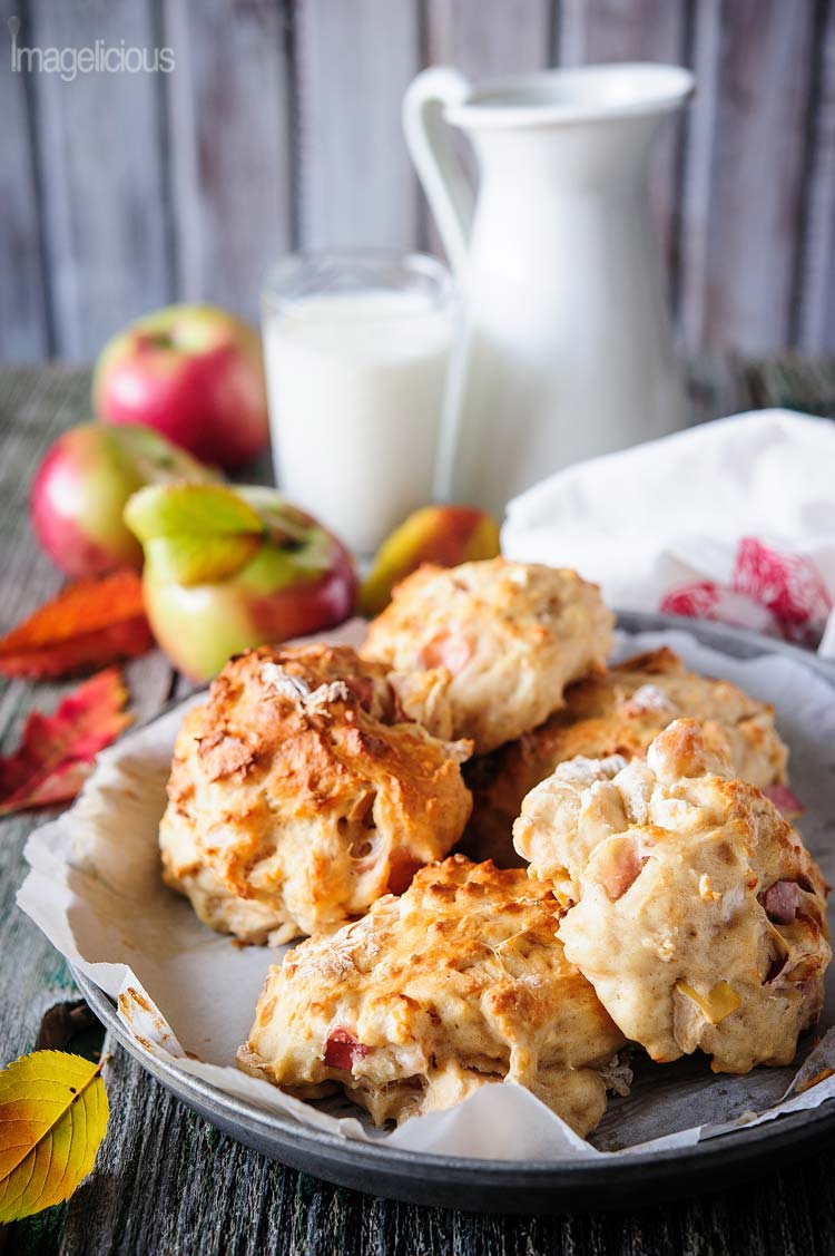 Plate of Apple Pie Rolls with some apples in the background, a jug, and a glass of milk