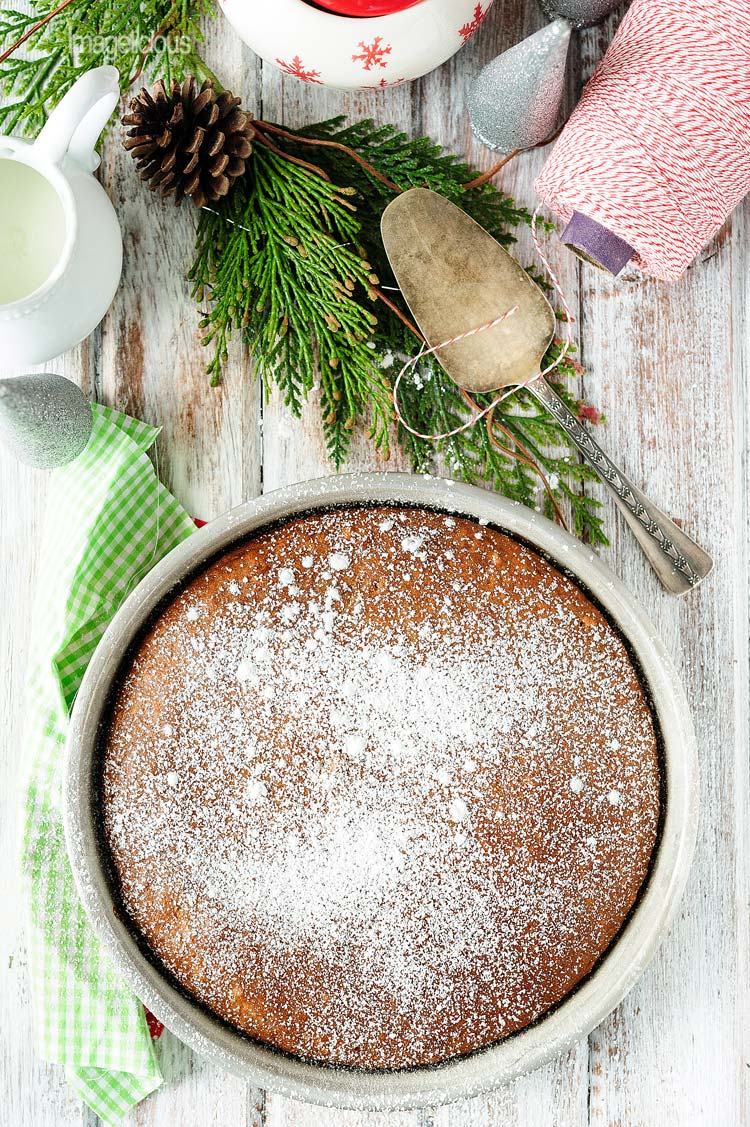 Top down view of Vegan Gingerbread Cake in a pan, covered in icing sugar. More christmas decorations are around the pan