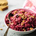 A bowl of beet salad with a few sprinklings of chopped pecans
