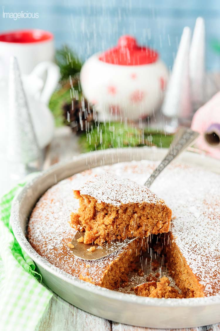 Vegan Gingerbread Cake in a pan with a slice cut out and half eaten, icing sugar is falling over it like snow