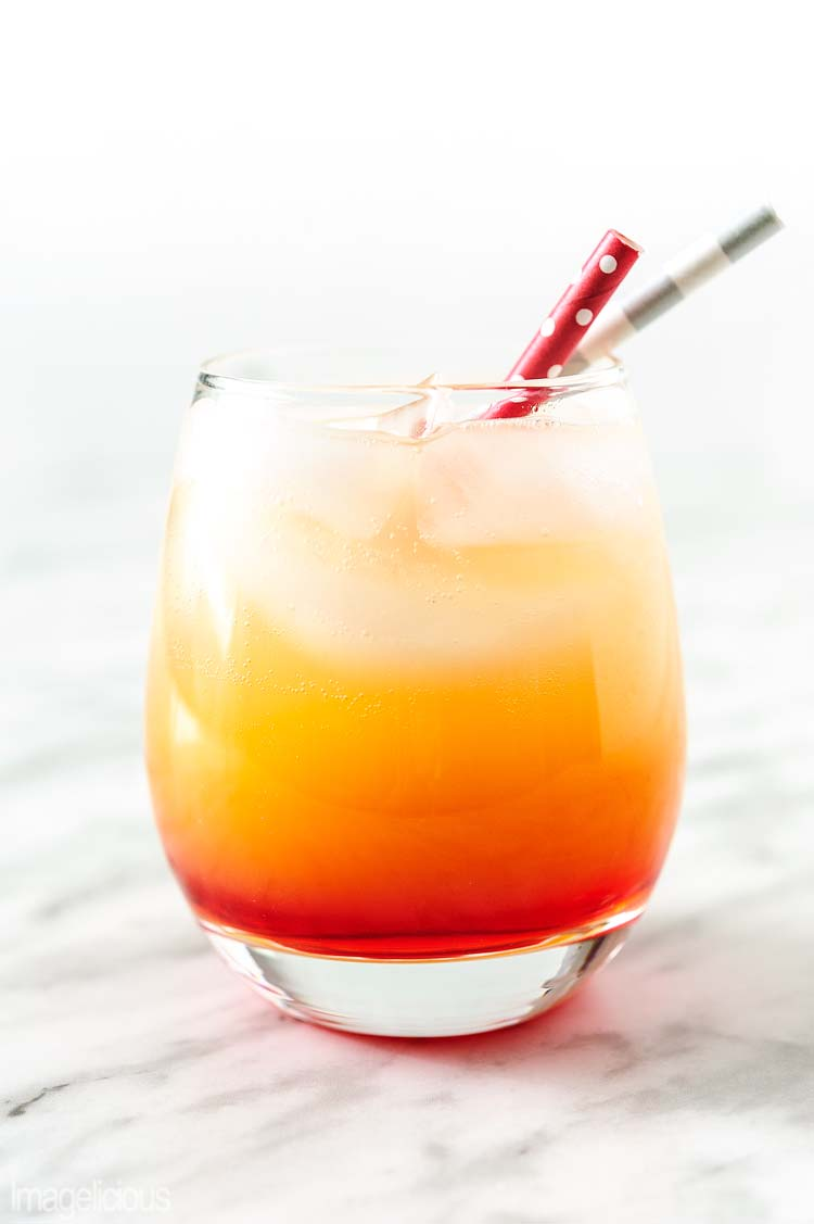 Glass on a marble top with two straws. In a glass there's a cocktail Campari Orange. Drink for the Easy Valentine's Day Menu for Two