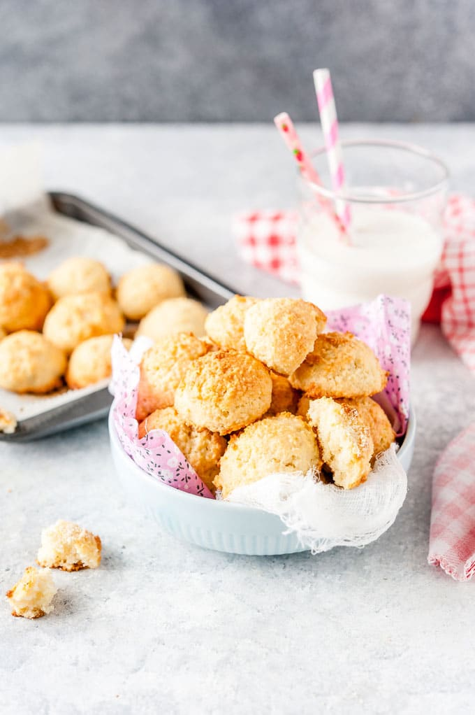 A bowl filled with Soft Almond Cookies and a few more cookies on the side on a sheet pan. A class of milk behind the bowl