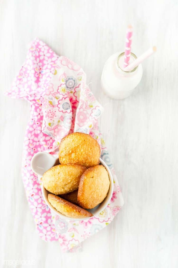 Bowl of almond cookies on a pink napkin with a little bottle of milk