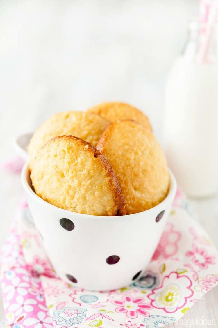 A small white bowl with black dots filled with Soft Almond Cookies. It is on a pink flowery napkin. A bottle of milk is visible in the background. Cookies are a dessert for the Easy Valentine's Day Menu for Two