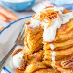 Close up of a stack of Carrot Cake Pancakes with a few pieces cut out
