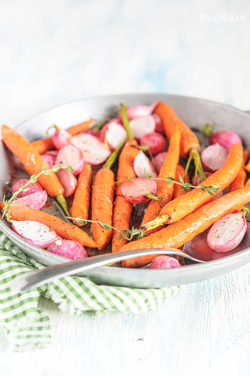 Round baking dish with roasted radishes and carrots with thyme and lemon
