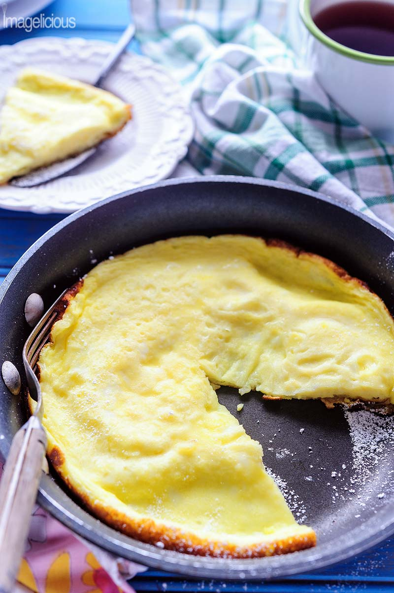 Sweet omelet in a pan with a slice cut out