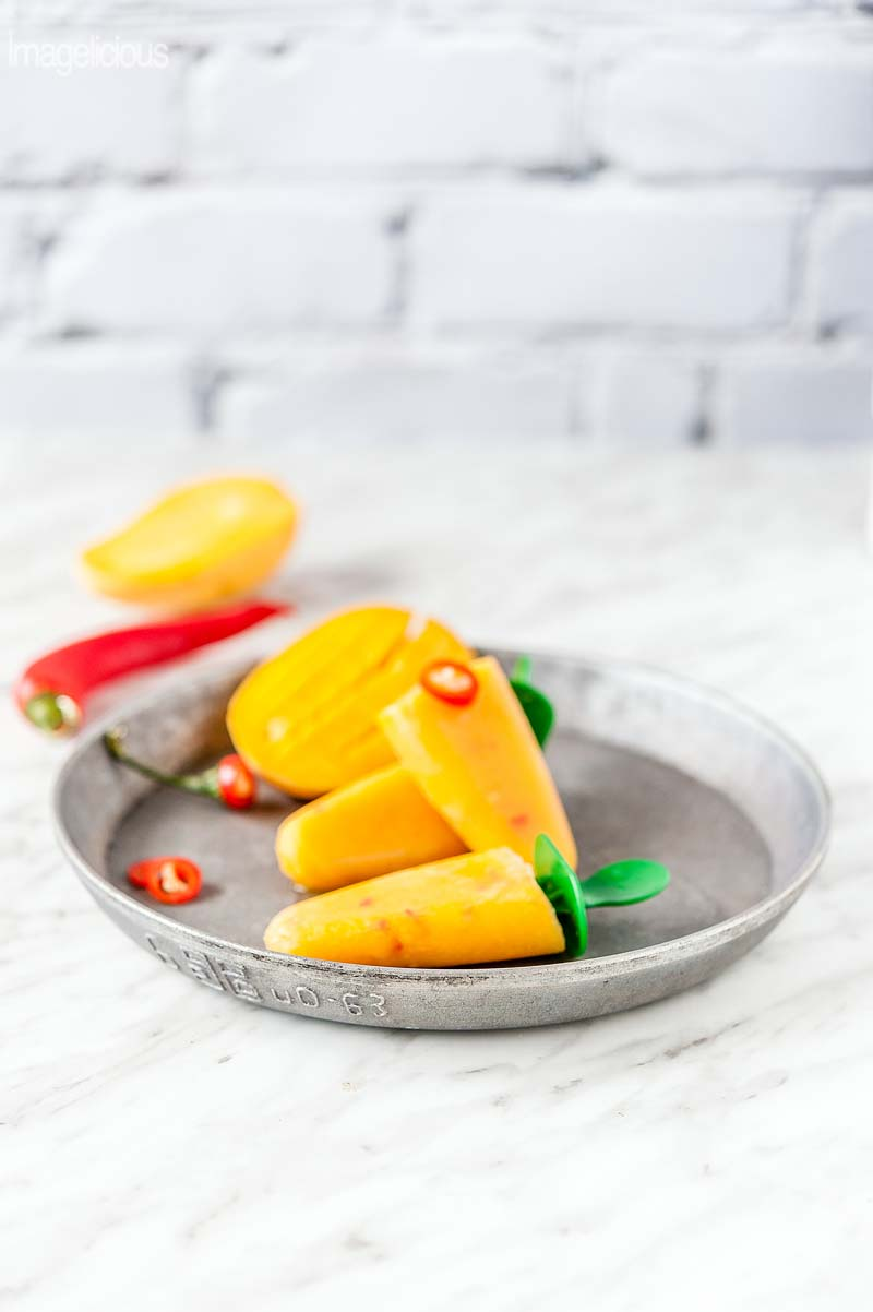 Photo of Mango Orange Chili Popsicles on a metal plate. Whole Chili pepper and two halves of a mango are visible in the background