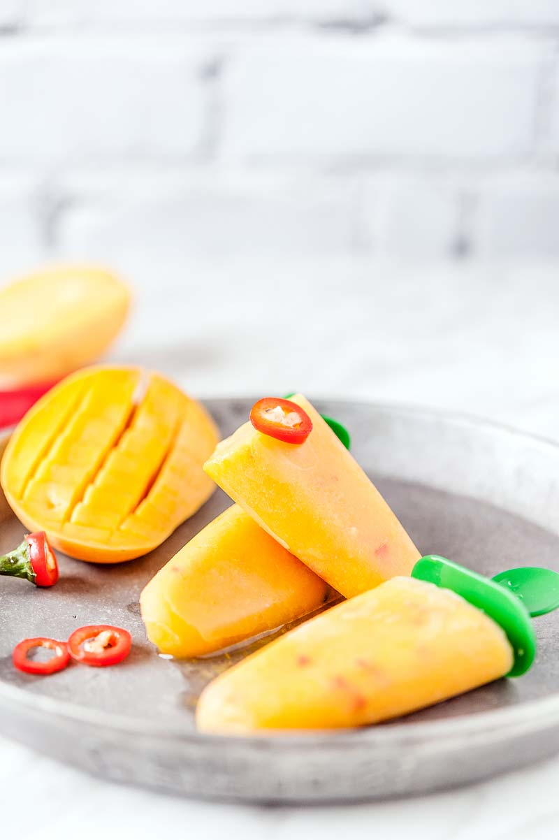Mango Orange Chili Popsicles are sweet, spicy, and refreshing. Great way to cool down in the summer. Chili pepper adds a fine spicy note to sweet fruit. Naturally sweet, vegan, raw, gluten-free | Imagelicious