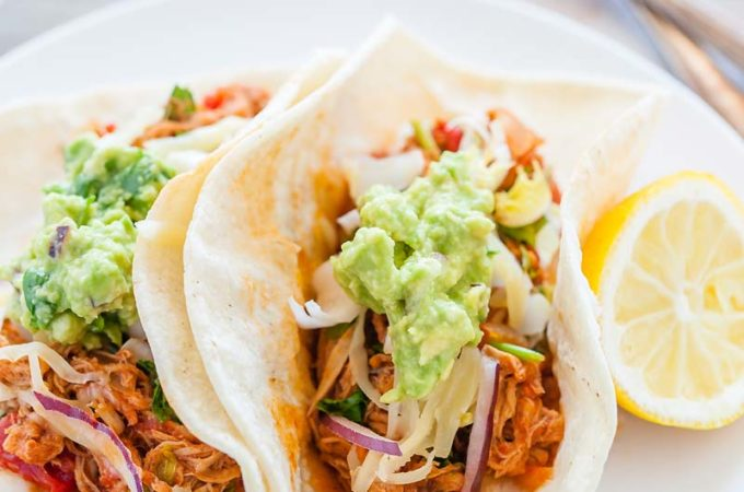 Pulled Pork Tacos are a great way to use up some leftover pulled pork. It's a fun meal that everyone will love. Add cheese, guacamole, and cilantro for a delicious medley of flavours. Great for picnics, family dinners, or busy evenings | Imagelicious