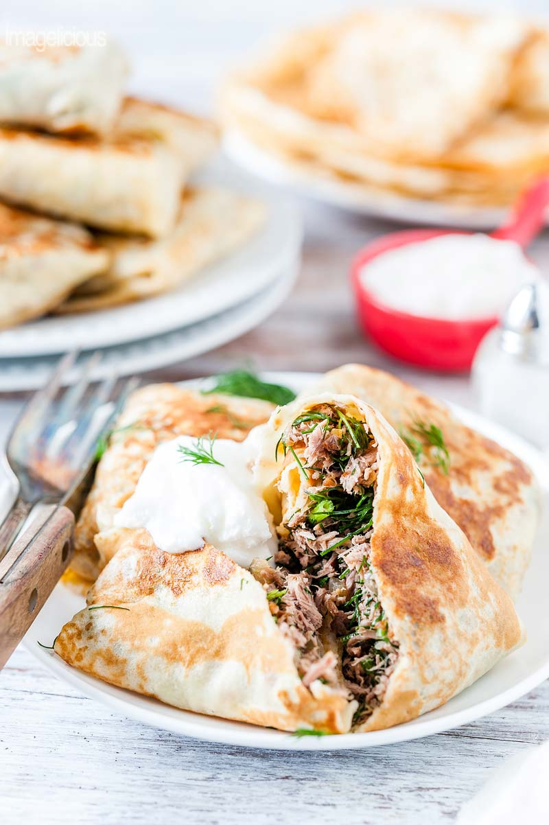 Close up of the plate of Beef stuffed crepes with one crepe cut open and beef and dill stuffing visible. A small bowl of sour cream and more crepes in the background
