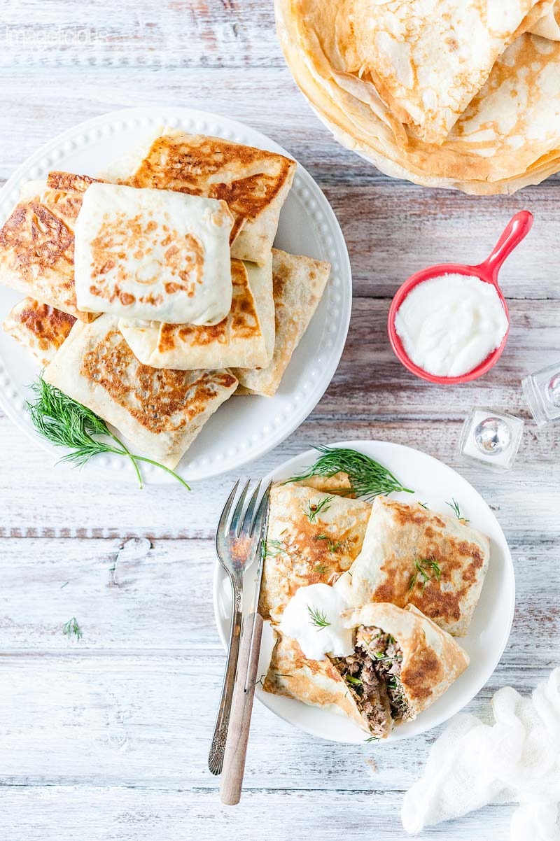 View from the top of a plate of Beef stuffed crepes with one crepe cut open. Another plate full of beef stuffed crepes higher up. And a plate of plain crepes at the top. Also shows a small bowl of sour cream