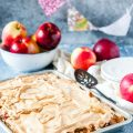 Sheet pan with Apple Meringue Tart in the forefront of the photo. A bowl with apples in the background. A few more apples around it. A stack of plates, napkin, and a cake server in the background.