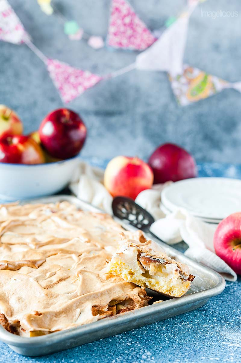 Sheet pan with Apple Meringue Tart in the forefront of the photo. One slice is cut and stuck on top of the rest of the cake so that the actual layers of pastry, apple, and meringue are visible. A bowl with apples in the background. A few more apples around it. A stack of plates, napkin, and a cake server in the background.