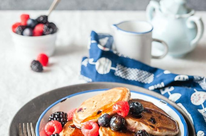 A plate of bumbleberry pancakes with a sprinkling of fresh berries on top, a bowl of berries in the background, and a jar with maple syrup, blue napkin and fork next to the plate.