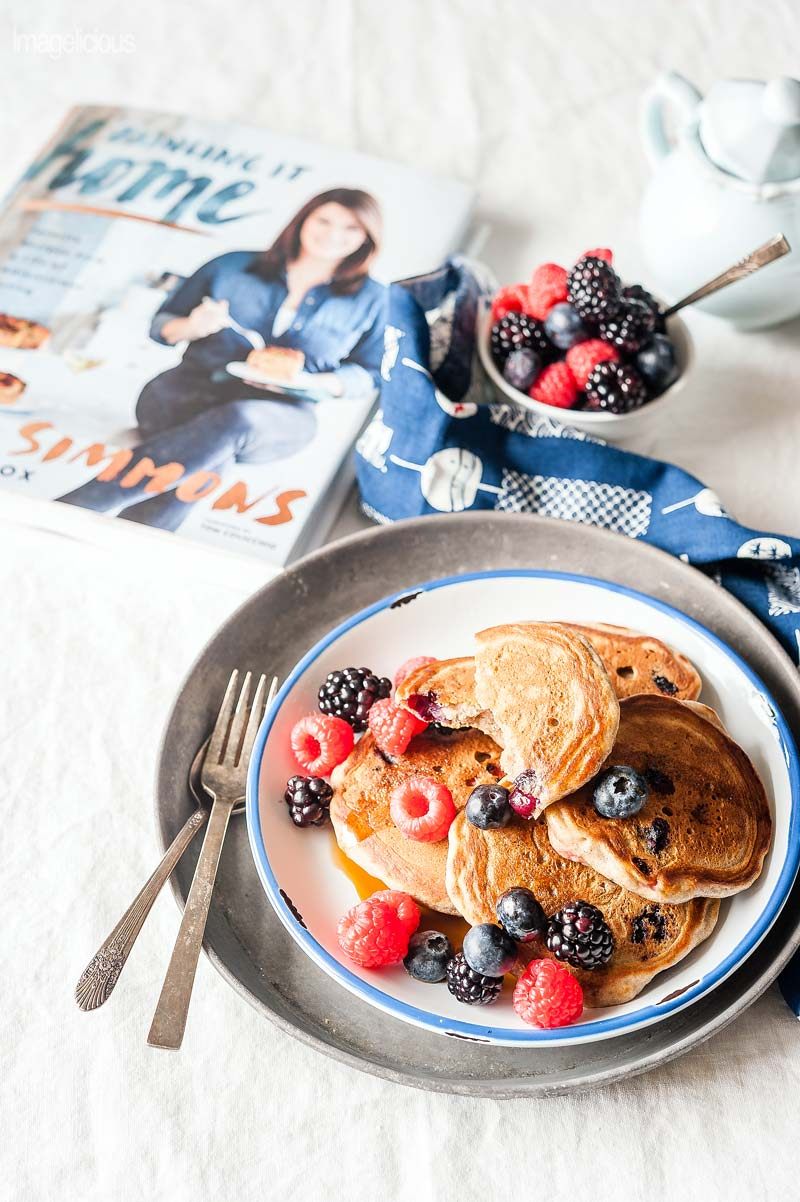 A plate of bumbleberry pancakes with a sprinkling of fresh berries on top, one pancake is cut in half, pancakes are covered in maple syrup. A bowl of berries in the background, blue napkin and fork next to the plate. A cookbook called Bringing it Home is in the background next to the plate of the pancakes