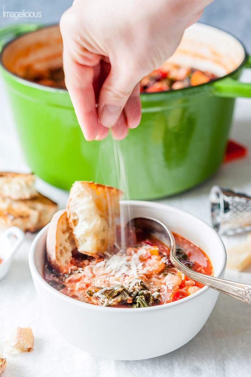 A bowl of vegetable soup called Ribollita with a few pieces of bread in it. Some bread and cheese is visible in the background. A big green pot of soup is behind the bowl. A hand is sprinkling cheese onto the soup.