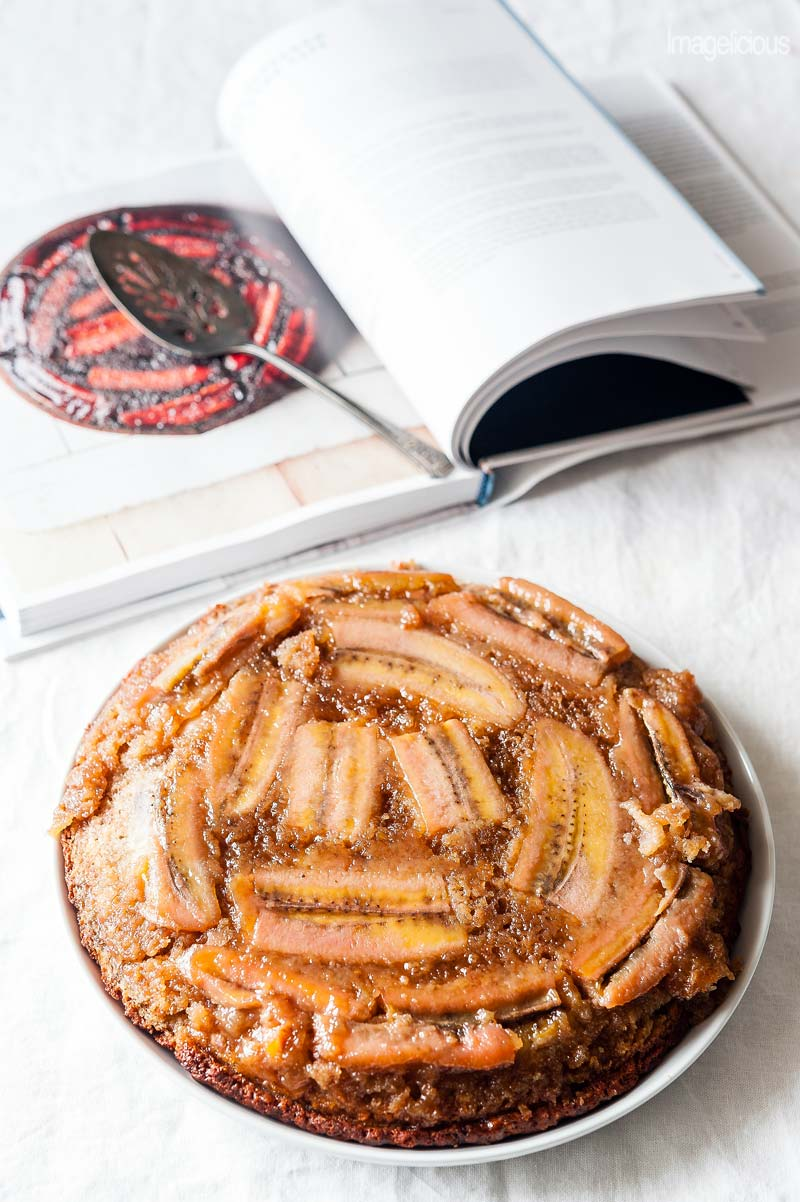 A plate with upside down banana cake and a cookbook open to a page with that same recipe and the picture of that same cake is in the background