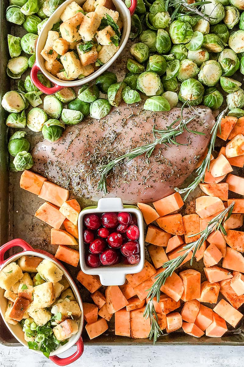 Sheet pan with food ready to go into the oven. In the middle of the pan there's a turkey breast with seasoning, around it brussels sprouts and sweet potatoes, also a small ramekin with cranberries and two ramekins with stuffing. A few sprigs of rosemary around.
