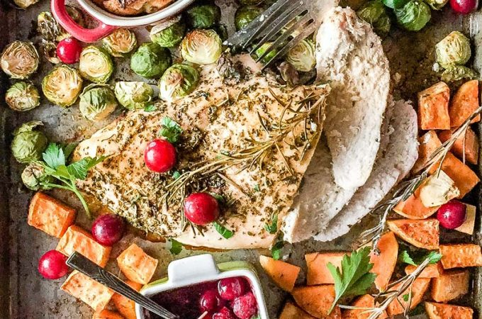 Sheet pan with cooked thanksgiving dinner. Turkey breast in the center of the pan with a few slices already cut, roasted brussels sprouts and sweet potatoes around the turkey. Two ramekins with cooked stuffing and a small ramekin with cranberry sauce. Parsley is sprinkled over everything. A knife and a fork are next to turkey