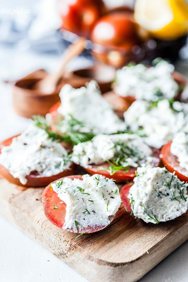 Close up of a wooden cutting board with slices of tomatoes that are smeared with goat cheese and dill spread
