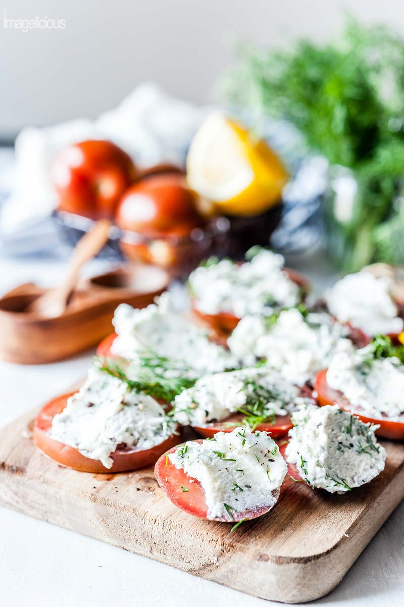 Wooden cutting board with slices of tomatoes that are smeared with goat cheese and dill spread