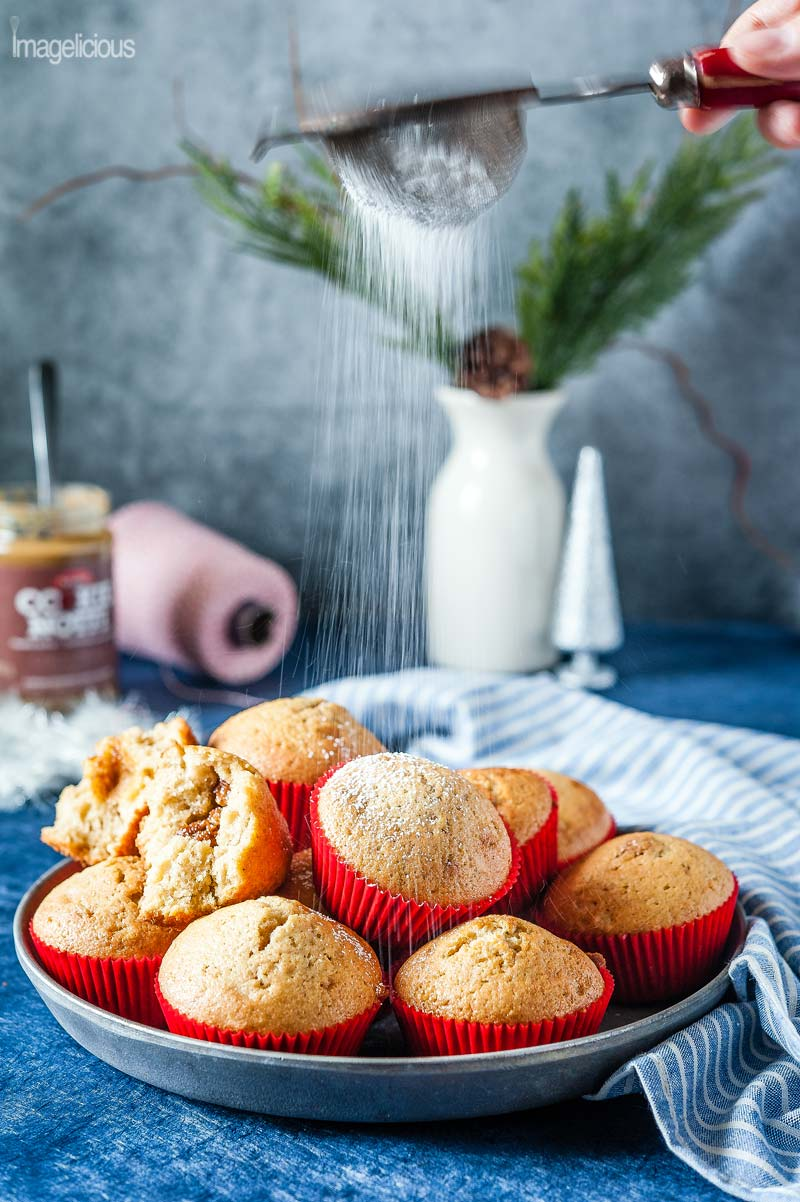 A plate of Cookie Butter stuffed cupcakes in red cupcake liners. A blue and white striped napkin to the right. A jar of cookie butter, red and white spool of string, small silver christmas tree, and a vase with greenery are in the background, all blurred. A hand holding a sieve is shaking icing sugar over the cupcakes.