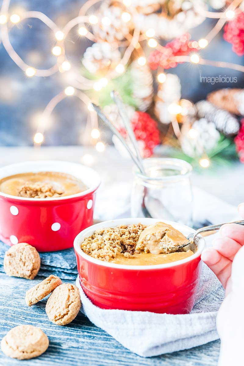 Two red ramekins with the gingerbread cheesecake and cookies scattered around. A hand is holding a spoon and scooping out some of the cheesecake from the front ramekin. Blurry christmas lights are in the background