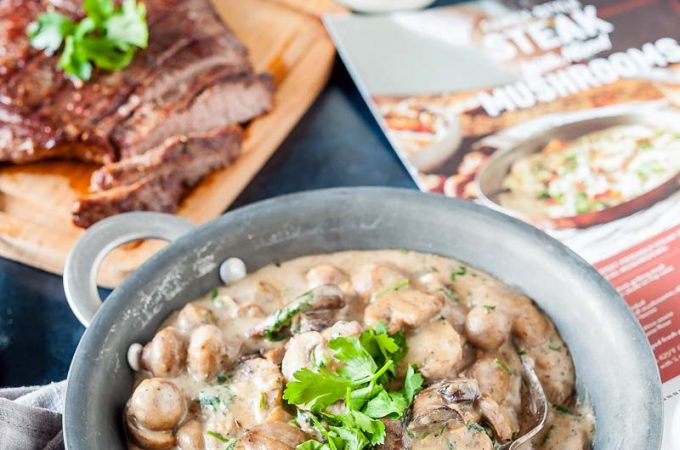 A pan with creamy mushrooms, a cutting board with the steak behind it, a calendar that's open to the page displaying this same recipe, a bottle of milk behind the calendar