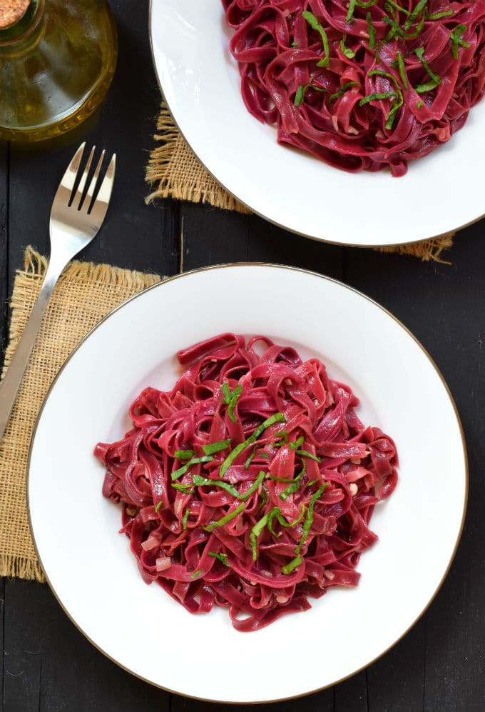 Top down view of two plates full of brilliantly red beet pasta
