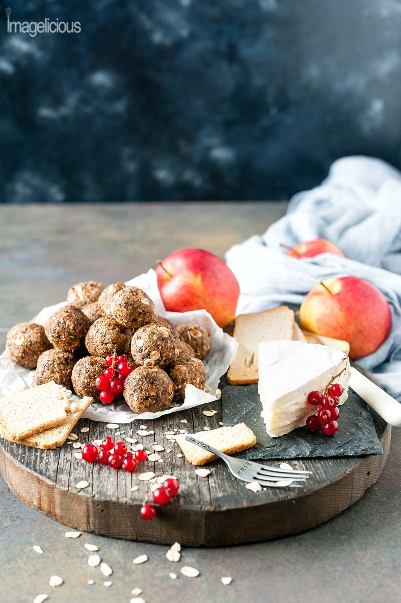 Cutting board with a wedge of brie cheese and a pile of Apple Pie Energy Balls on a piece of parchment paper. A few crackers are scattered around. A few apples are visible in the background with a napkin. A few red currants are also on the cutting board