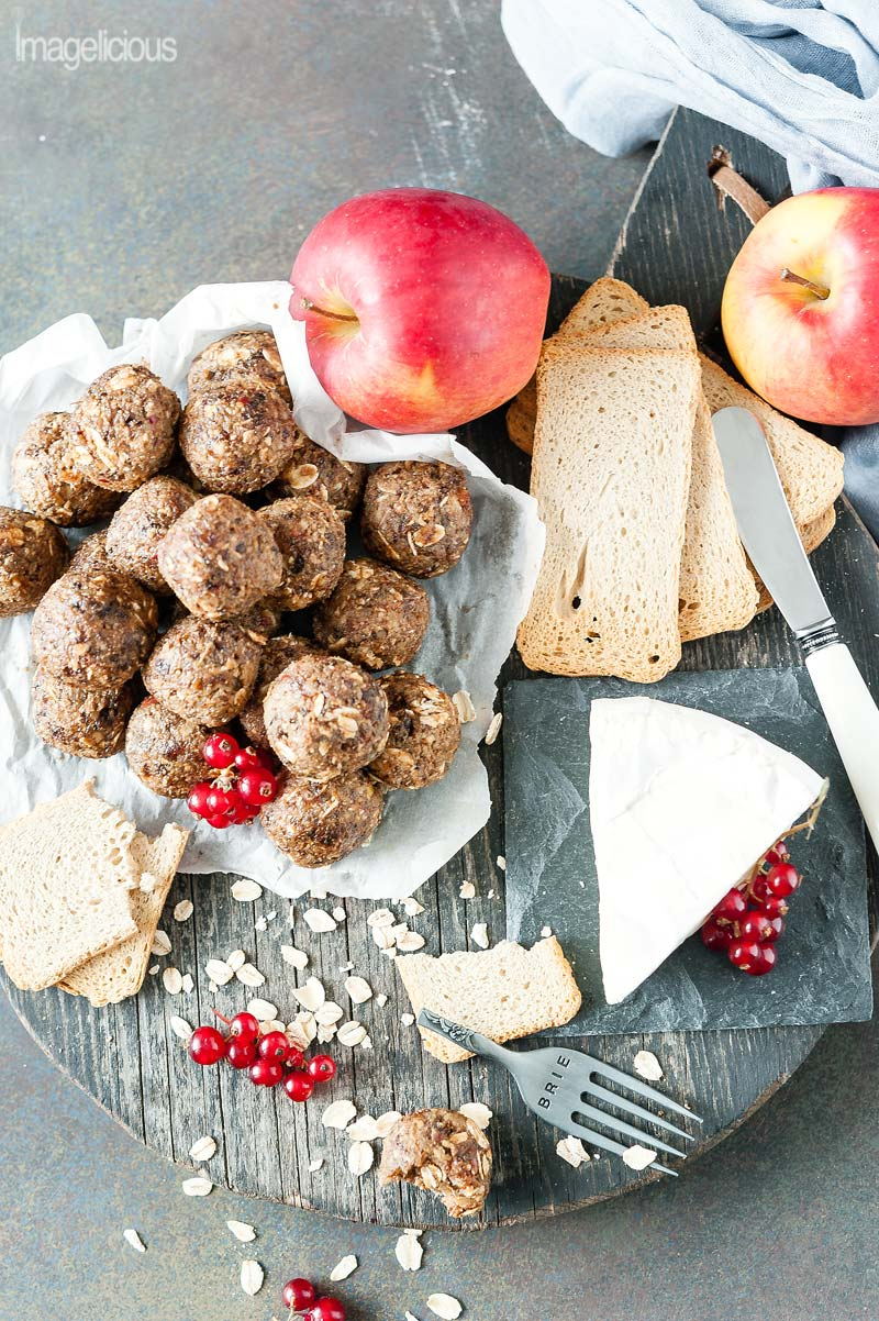 Top down view of a cutting board that holds a small wedge of brie cheese, a few crackers, and a pile of Apple Pie Energy Balls on a piece of parchment paper. A few red currants are scattered on a cutting board along with oats, crackers, and apples