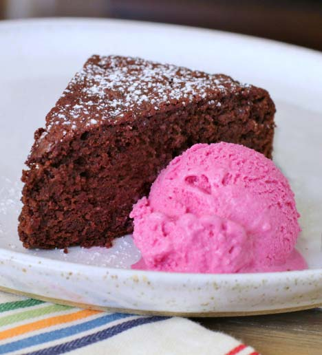 A plate with a slice of chocolate beet cake and a scoop of pink beet ice cream
