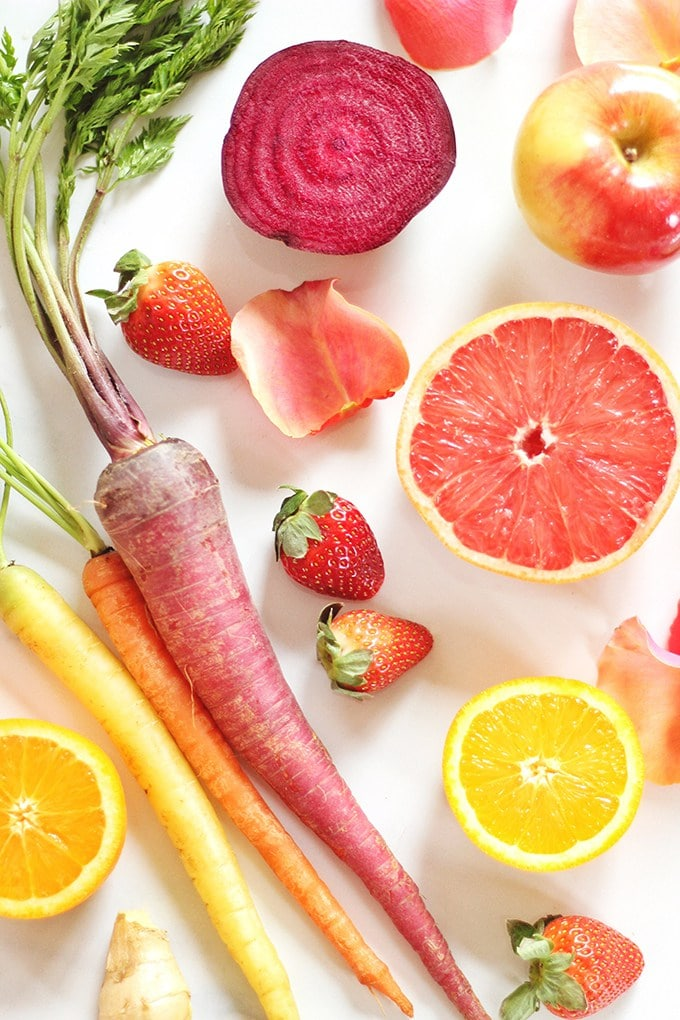 Top down view of brightly coloured fruits and vegetables including beets, carrots, oranges, and grapefruit