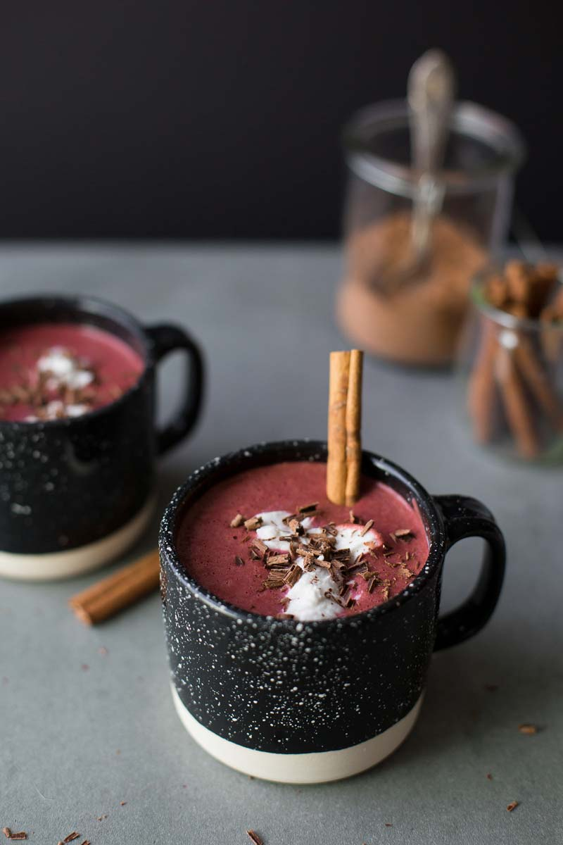 Close up photo of two mugs filled with pink hot chocolate and a cinnamon stir sticks
