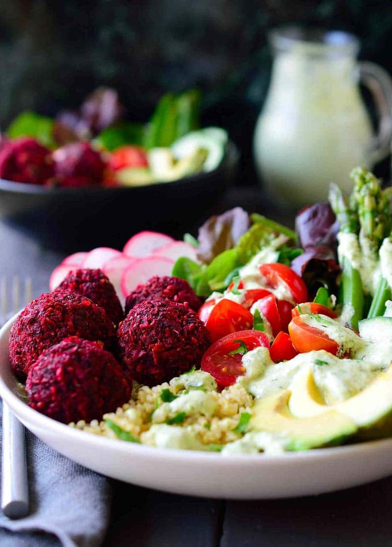 A bowl filled with vegetables, avocado, and beet falafels