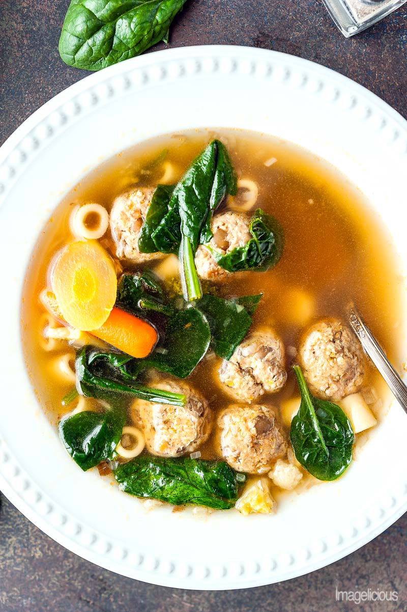 Top down and closeup view of a bowl of soup made with Lentil-Turkey Meatballs, short pasta, spinach, and vegetables
