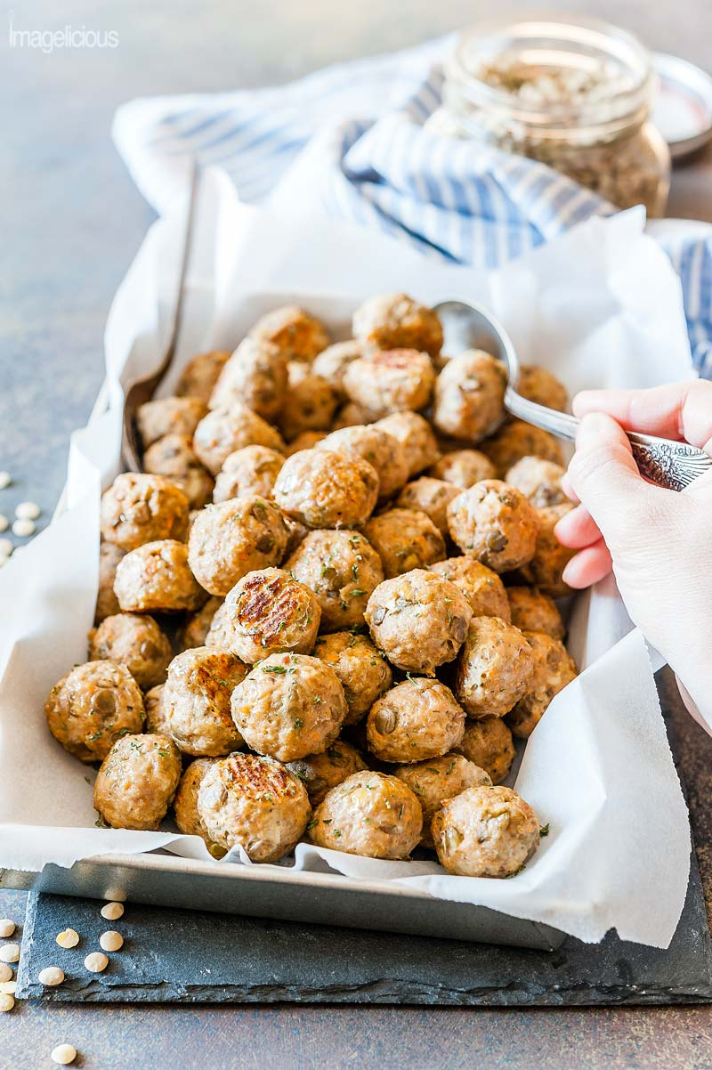 Big tray lined with parchment paper and filled with Lentil-Turkey Meatballs is on a black slate board. A hand is holding a spoon scooping out the meatballs. A jar of lentils is visible in the background