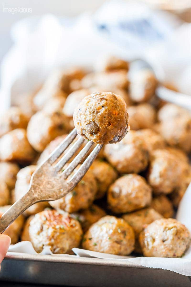 Closeup of a fork holding a Lentil-Turkey Meatball with a tray of the rest of the meatballs visible in the background, blurry.