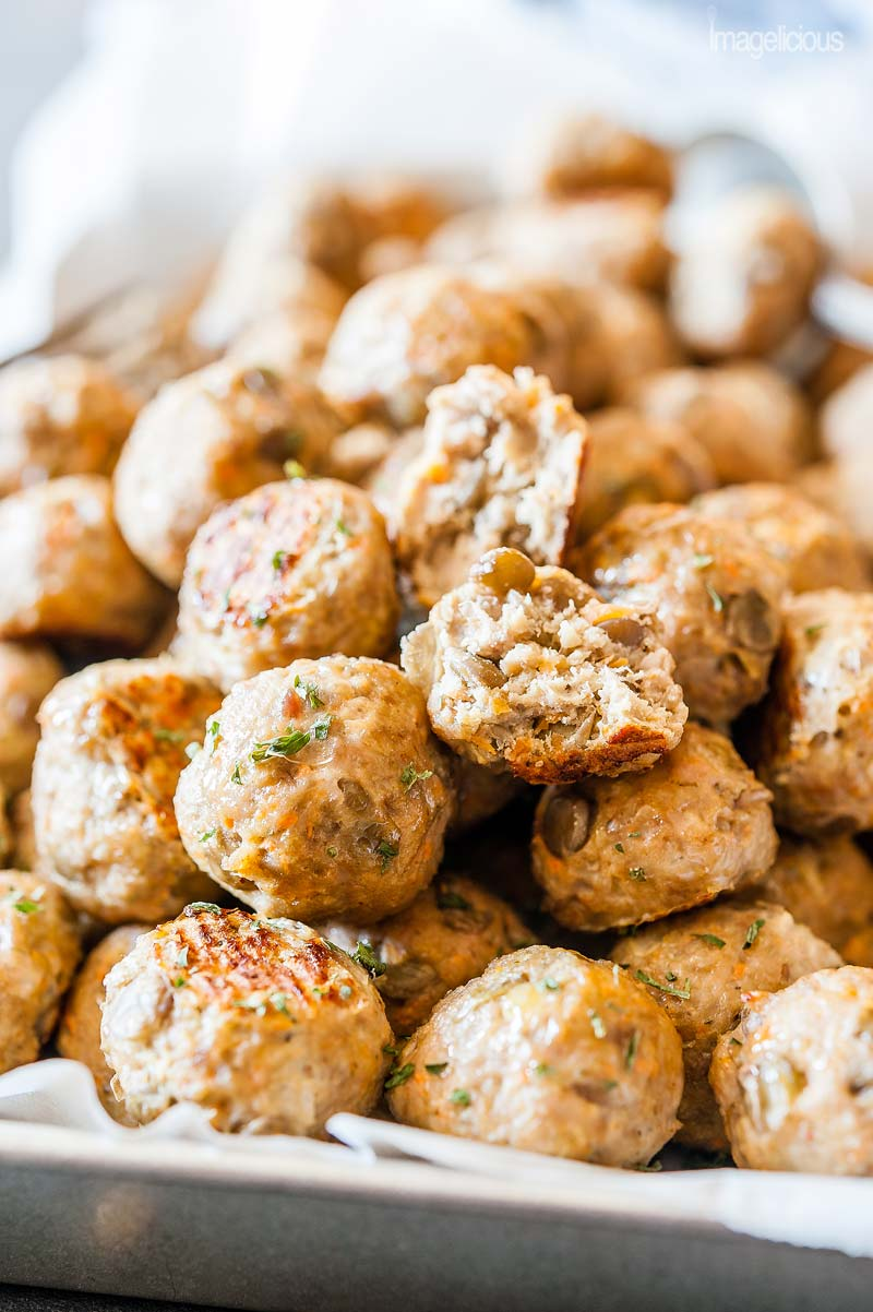 Closeup of a tray of Lentil-Turkey Meatballs with one of them split in half so that the texture of the meatballs and lentils is visible