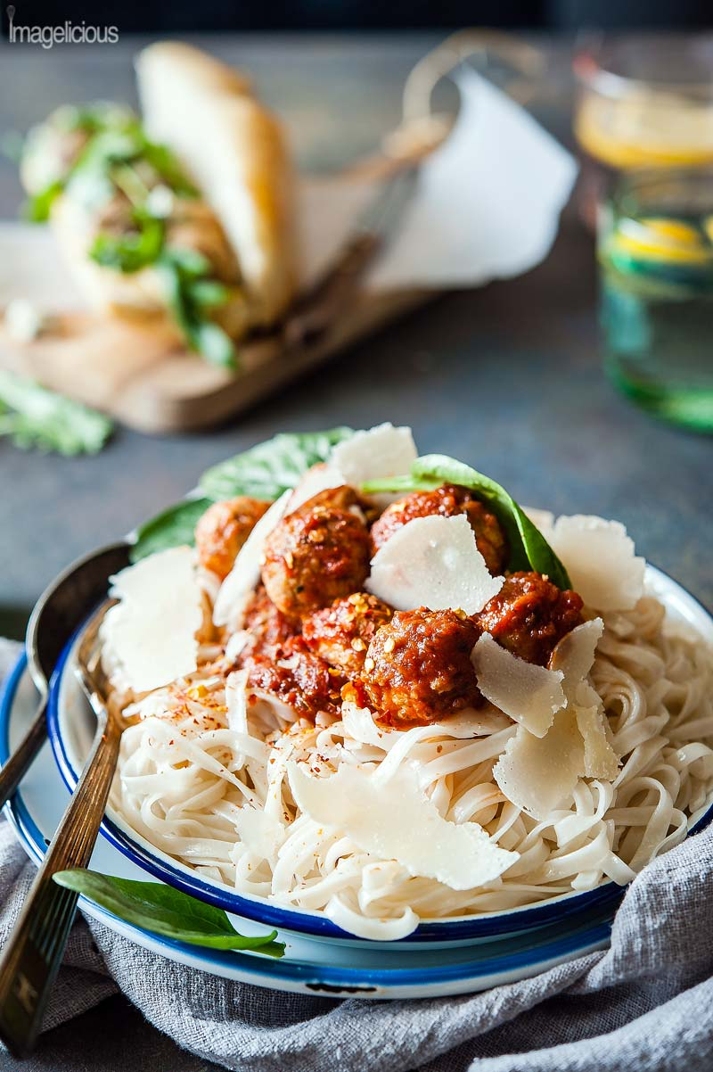 Closeup of a plate of fettuccine noodles with a big scoop of tomato sauce and Lentil-Turkey Meatballs. A few spinach leaves are visible on top of the pasta. Red hot chili pepper flakes are sprinkled over the sauce and a few shavings of parmesan are on top. More food is visible in the background, blurred.