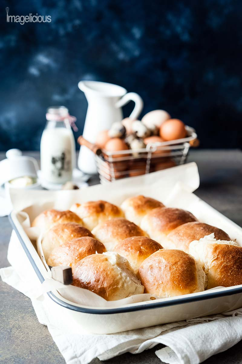 Pan with 12 beautifully goldent Instant Pot No Knead Dinner Rolls. A basket of eggs, white pitcher, small bottle with milk are in the background