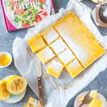Top down view of cut up Coconut Lemon Bars with more lemons, zest around them. A small plate with a bar and a fork is there. Also a cookbook Simply Citrus is next to the bars and a postcard with pictures of various citrus fruits